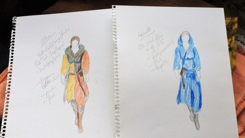 Sketches of possible costumes for the two leads.